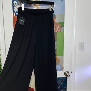 Loose black trousers / with a belt